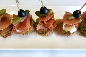 С сырокопченым окороком и корнишоном на ржаном хлебе с домашней горчицей, с салатом и маслиной.